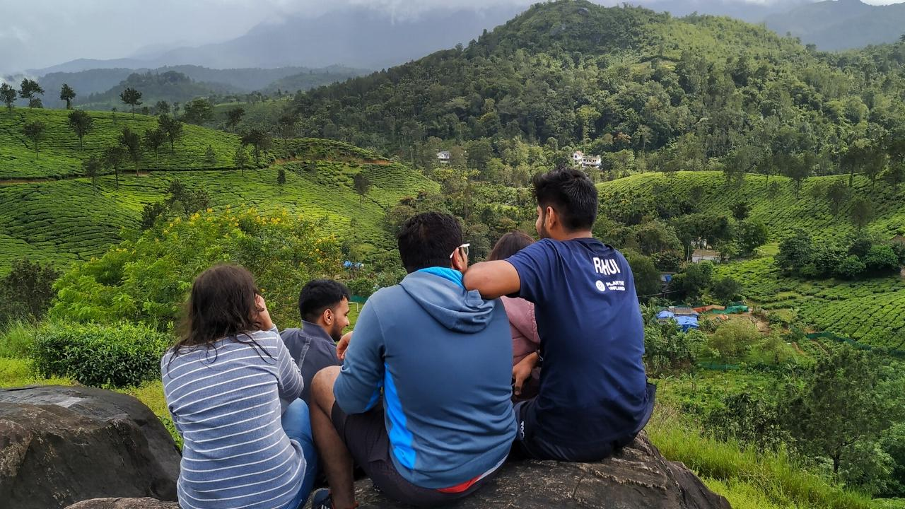 sitting together and enjoying a view of the lush Wayanad hills