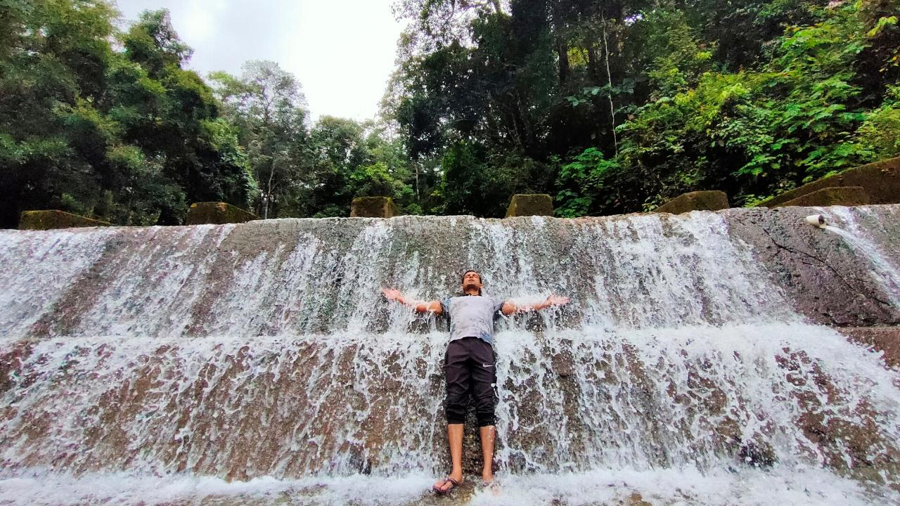 a trekker under a small waterfall on the wayanad night trek